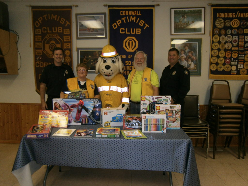 Left to right: Firefighter  Ian Robertson, Toy Drive Chair  Anita Tremblay,   Sparky, Optimist President  Ralph Brunton, Captain James McDonald
